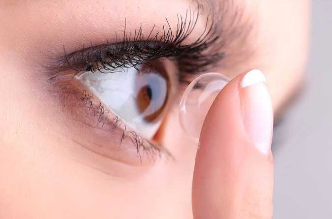 young woman approaches contact lens to eye