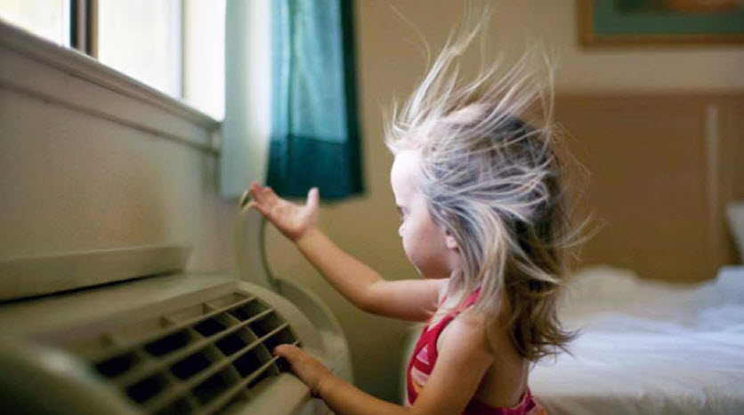 little girl standing in front of air conditioning unit